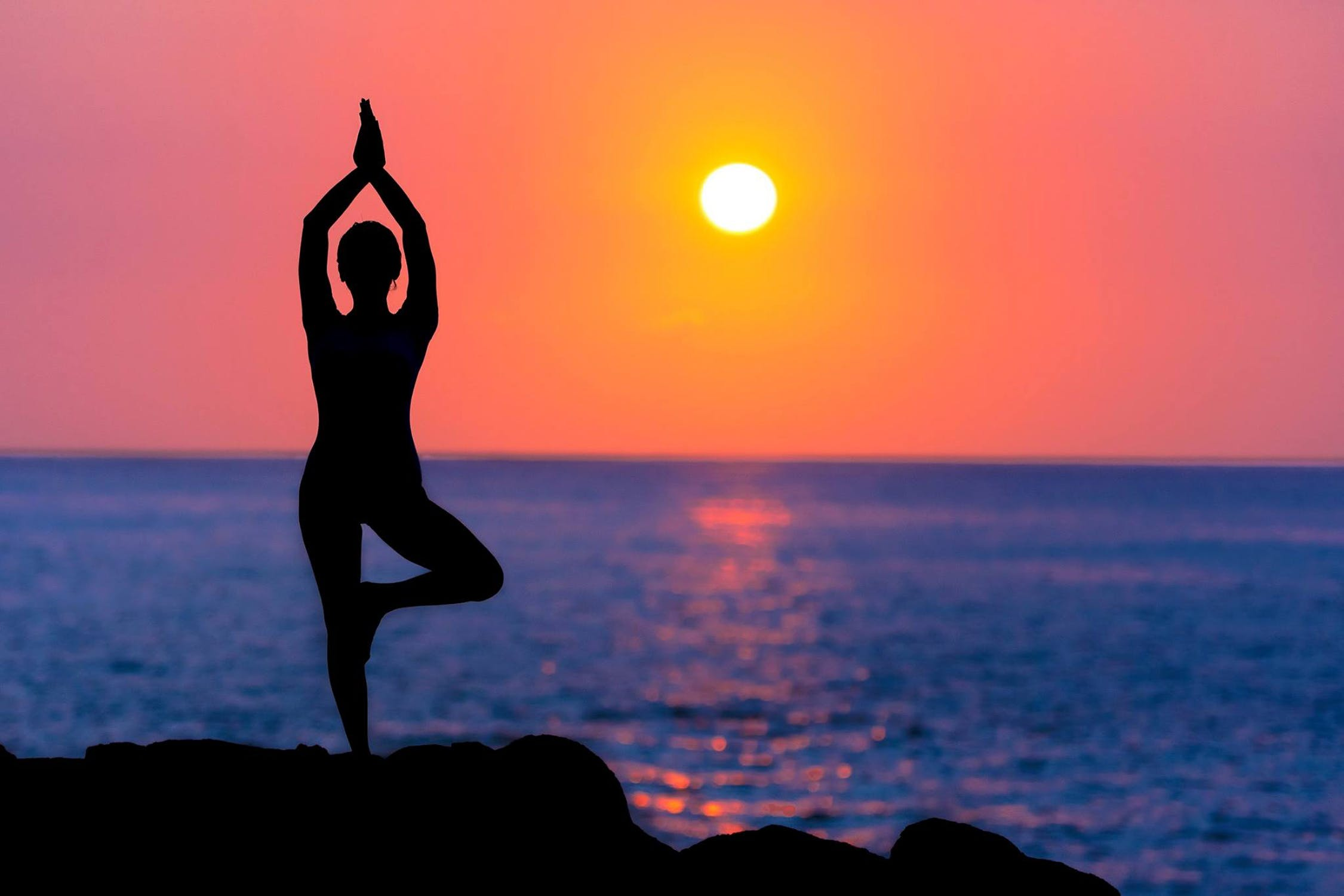 Woman practicing yoga in tree pose during sunrise