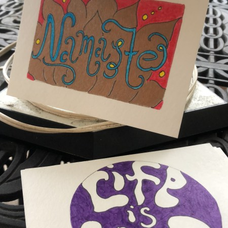 greeting cards that say namaste and life is good on a table