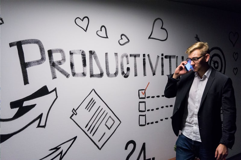 man on cell phone walking by a wall with the word productivity on it