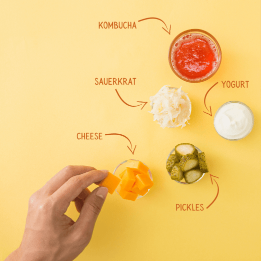 Prebiotic. On a yellow background, there are 4 small bowls. One filled with cheese, another with chopped pickles, third with sauerkraut, and the fourth with yogurt. There is also a clear glass of red kombucha tea. The same hand is in the shit holding a cube of cheese between the thumb and index finger.