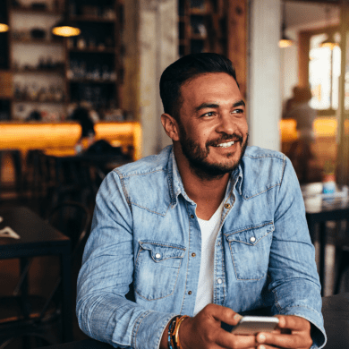A man is smiling, thinking about how he has improved his mental wellness through managing his money with a money tracking app like nav.it