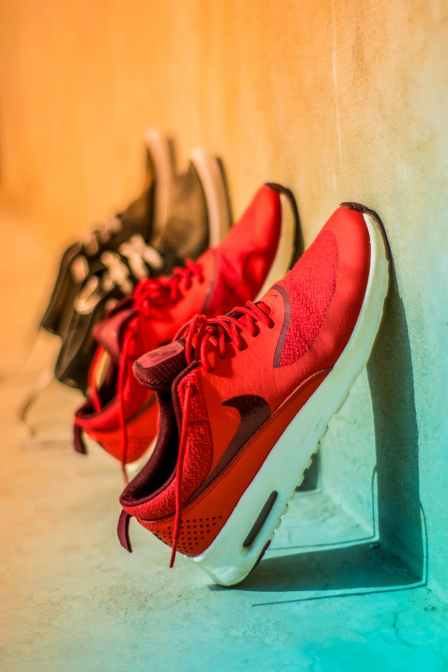 focus photography of pair of red nike running shoes