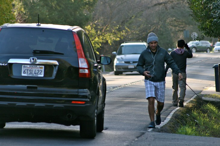 Neighbors dodge cars and other pedestrians alike along Walnut Boulevard.