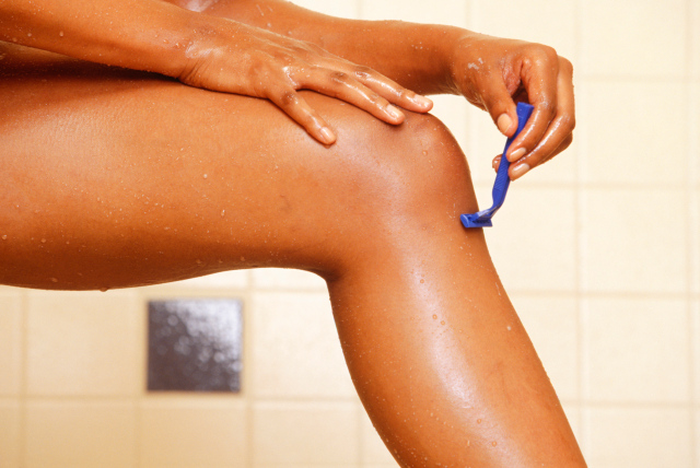 Woman shaving legs in shower, low section, close-up