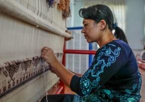 Eine usbekische Frau arbeitet am Webstuhl