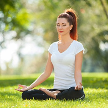 Woman sitting on grass in a yoga pose.