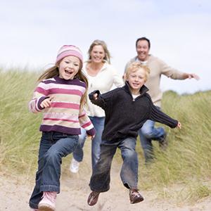 Family running on beach smiling