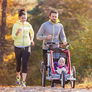 Picture of a healthy couple running with their baby.