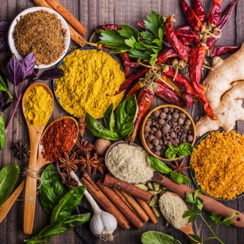 Heaps of different spices on a wooden background