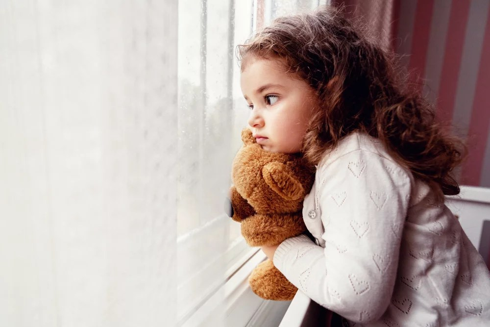 dziewczynka patrzy. na deszcz za oknem