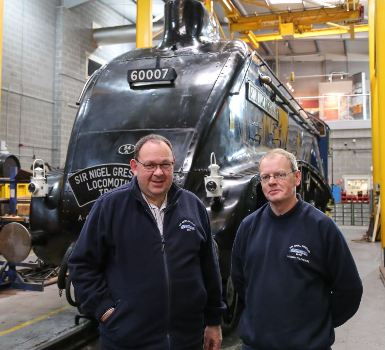 John Wilkinson (left) and Darrin Crone stand proudly on The Works floor in front of the loco.