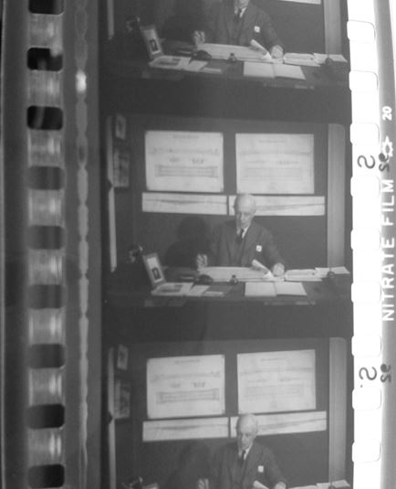 "This is a picture of a 35 mm safety print (acetate base) of the black and white sound film ""The Kearney Monorail"" (another film about the Kearney Railway). On top of the picture, below the perforation you can see the optical sound track, then the frames, and on the edge below the perforation in the bottom of the picture the printed ""Nitrate film"" and blast symbol in white on a grey back ground. These were printed on this safety film from a previous nitrate negative element."