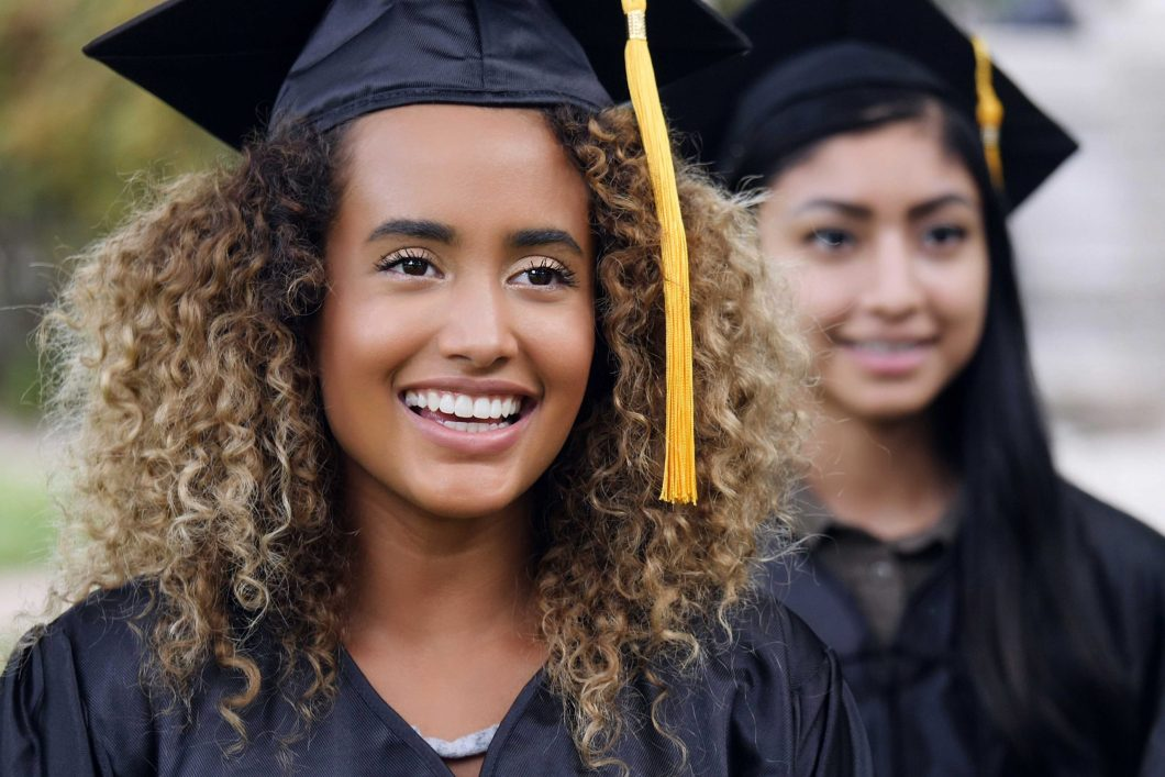 Two female students in graduation caps and gowns