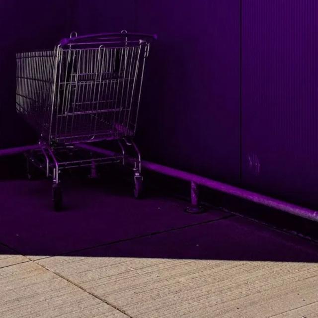 Un carro de supermercado en una esquina formada por dos paredes sobre fondo morado.