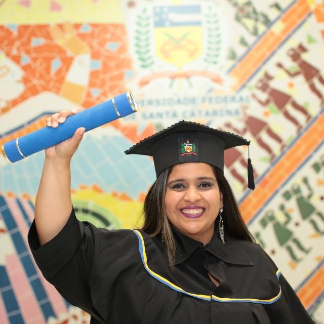 Paula Hurtado, Product Manager de Nu, alzando su título, vestida con una toga.