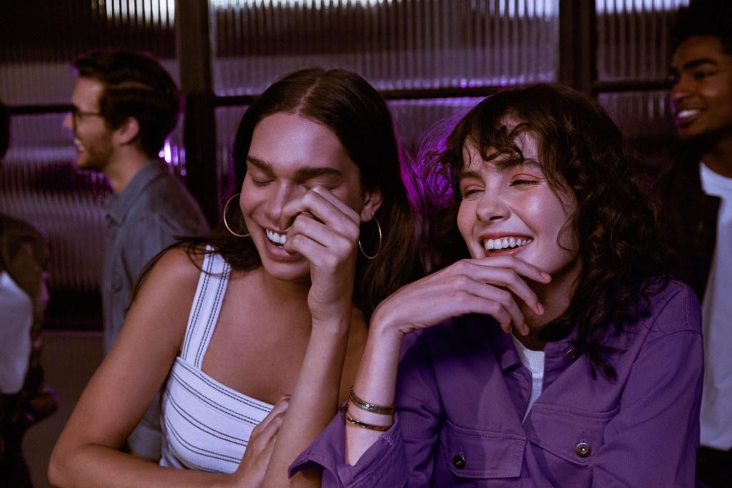 Dos jóvenes mujeres sentadas ríen y la cámara la toma en el preciso instante en que tienen ambas los ojos cerrados, en plena carcajada.