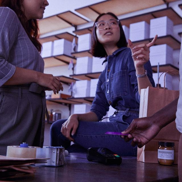 Una mujer vestida con un enterito de jeans y anteojos está sentada en una mesa delante de unos anaqueles con cajas; habla con dos personas: una de ellas sostiene la tarjeta de crédito Nu.