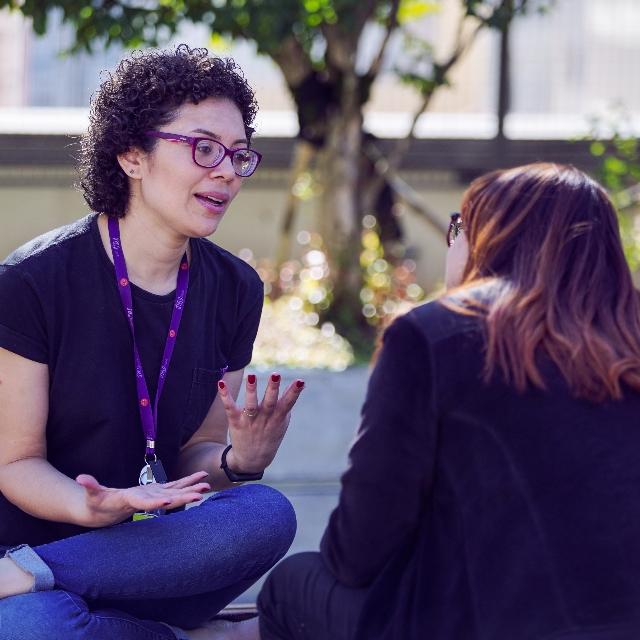 Una mujer joven con cabello rizado y gafas moradas está sentada en un parque y, por la posición de sus manos, parece explicar algo a otra m mujer de manera enfática.