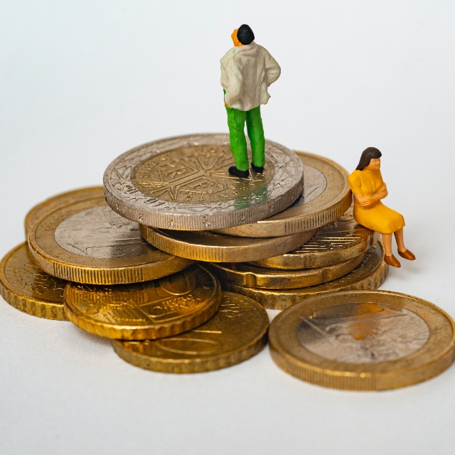 Dos muñecos en miniatura sobre una pila de monedas se pregunta