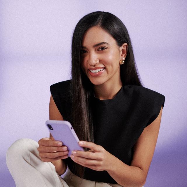 Una mujer joven, morocha, sonríe mientras sostiene un celular de color lila