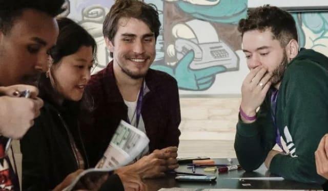 Código Nu: Un grupo de jóvenes sentados al rededor de una mesa hablan sobre planes de trabajo