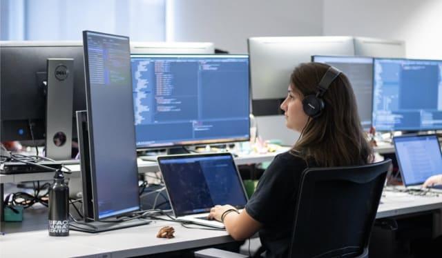Chica con audífonos programa con lenguaje Clojure en computadora disfrutando trabajar en Nu