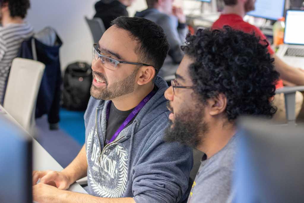 Dos chicos de mediana edad con anteojos hablan y sonríen frente a una pantalla
