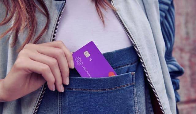 Controla tus movimientos desde la app Nu: chica guarda su tarjeta de crédito Nu en su bola delantera