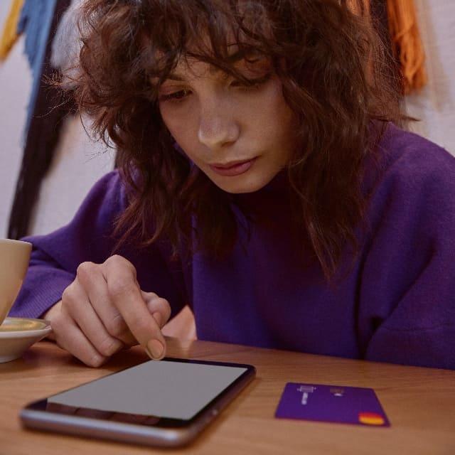 Adolescente observa su distribución de gastos por categoría, en la app Nubank.