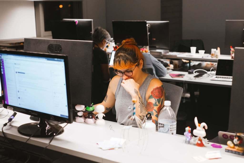 Clojure: Una mujer joven con anteojos de marco y su cabello teñido parcialmente de naranja, una musculosa gris y rosas estampadas en su brazo izquierdo, parece pensar enfrente de su computadora.
