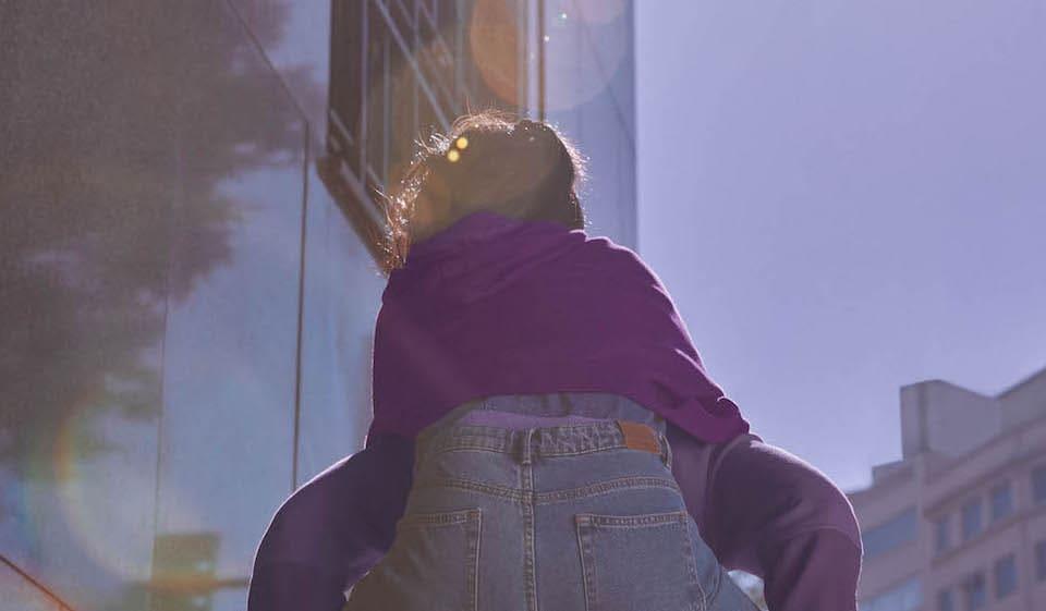 Dos mejores amigos vestidos de morado, con un estilo casual, corren hacia la luz del sol.