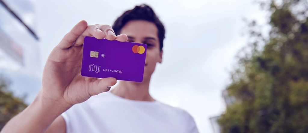 Nu llega a Colombia: hombre joven de playera blanca sostiene tarjeta de crédito Nu