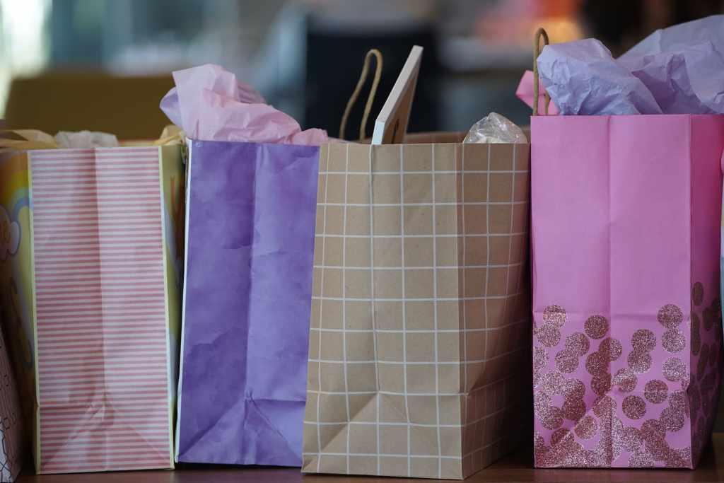 Bolsas de papel morado y rosas que invitan a planear los gastos y a aprovechar el aguinaldo