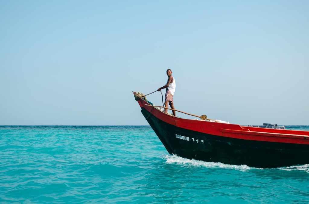 Hombre navega en el mar caribe sobre una lancha negra: viajar a Meses Sin Intereses con Nu en Despegar y Best Day