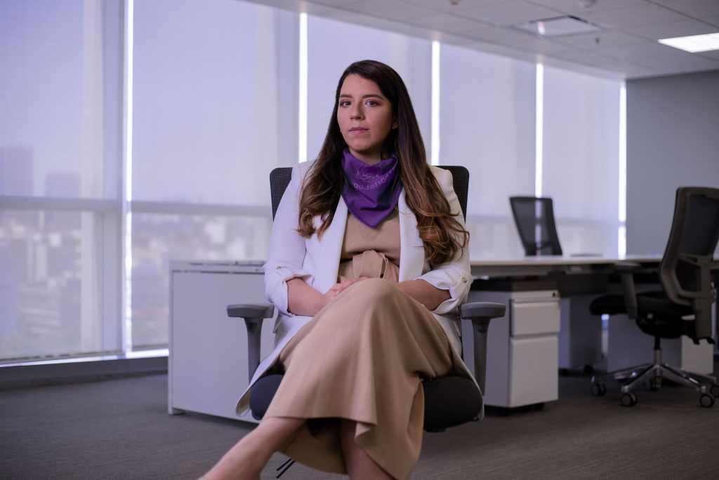 Michelle Naranjo en las oficinas de Nu México, vestida con un saco blanco y una pañoleta morada que muestra su empatía en el día internacional de la mujer