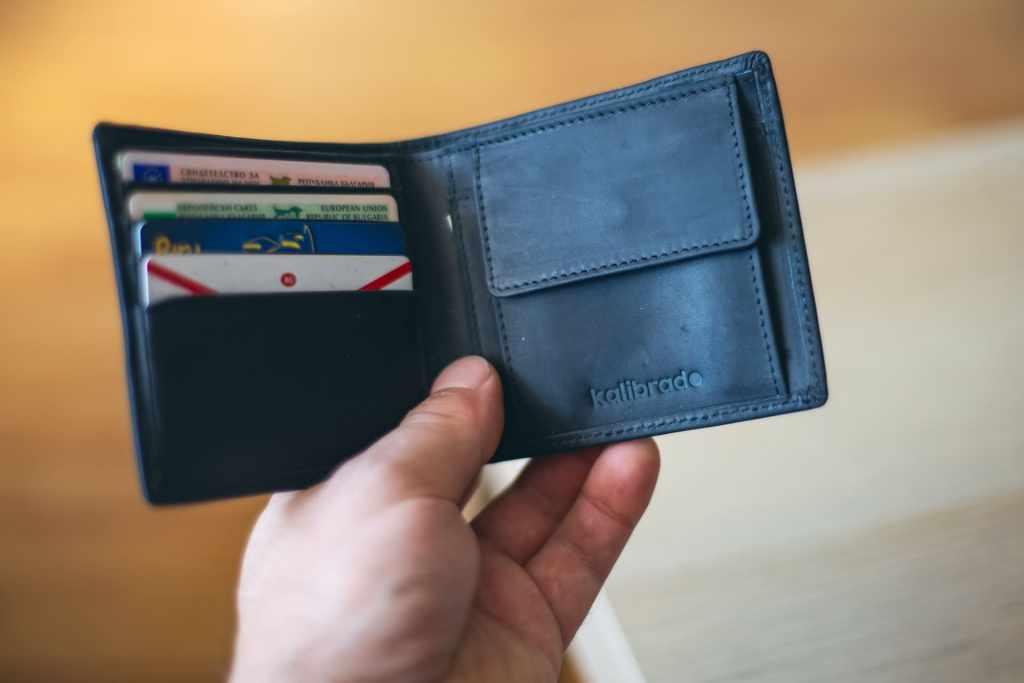 Hombre abriendo cartera de piel color negro se da cuenta que ha sido víctima de robo de datos personales e identificaciones