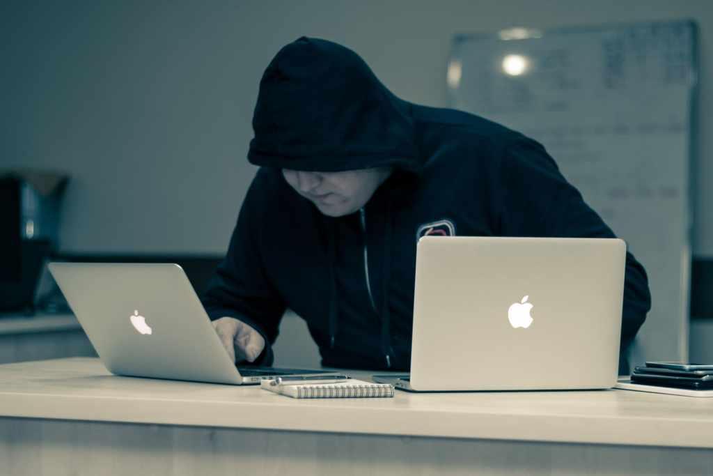 Hombre con sudadera negra trabaja sobre dos computadoras robando información y haciendo ATO o robo de cuentas.