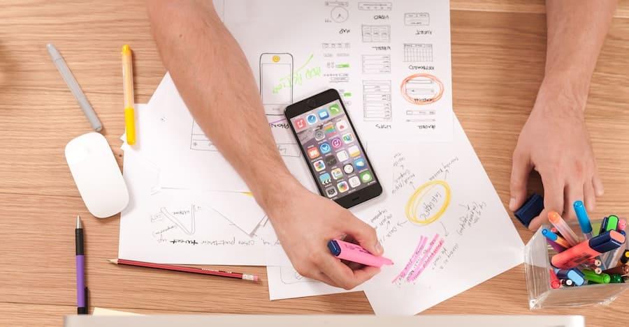 Papeles de cuentas, estados de cuenta, plumas, marcadores y un celular sobre una mesa de madera sirven a un hombre para hacer su día financiero
