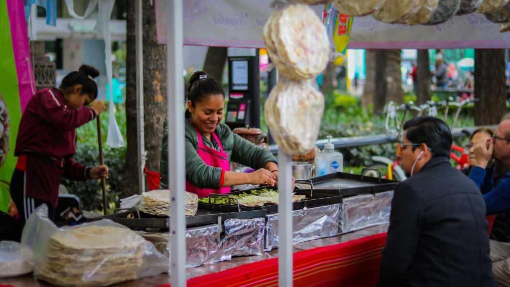 Mujer mexicana con sudadera verde y mandil rosa atiende un puesto de comida callejera para cambiar su futuro