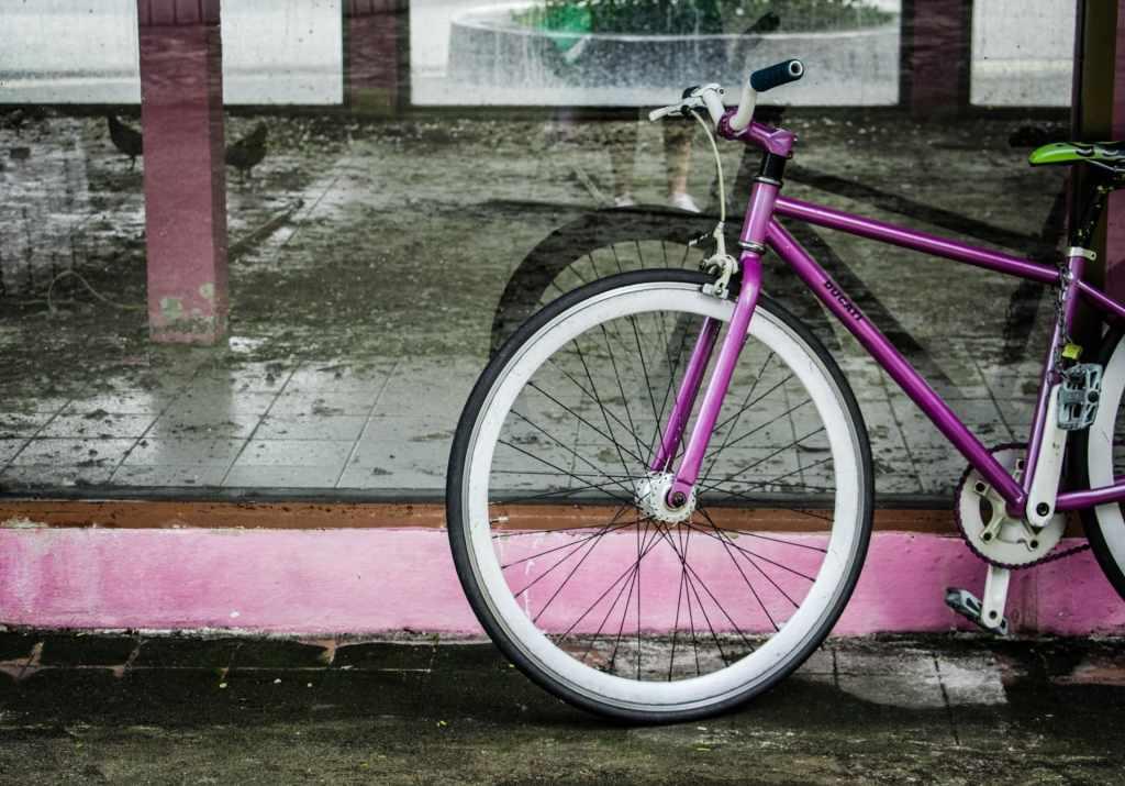 Bicicleta color morado recargada en una ventana una alternativa de movilidad para replantear ¿cuánto gastar en transporte?