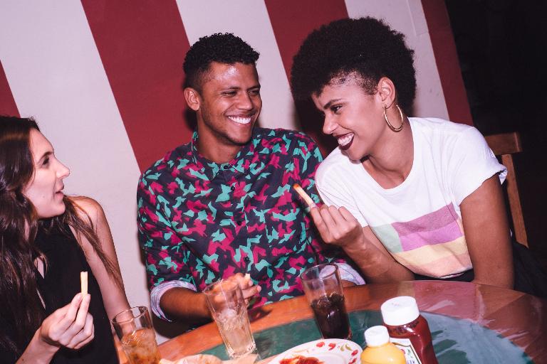 Três amigos sentados em uma mesa, tomando refrigerante e comendo batata frita. Há duas moças e, entre elas, um rapaz.
