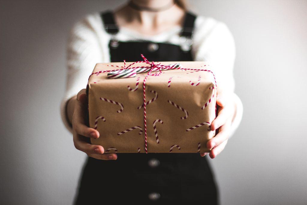 Jovem segura um presente embrulhado em papel craft, com uma fita vermelha e adesivos de bengalas natalinas colados