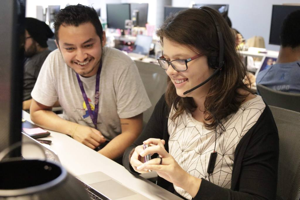 Um homem e uma mulher sentados em frente ao computador, sorrindo. Ela está usando um fone com microfone embutido