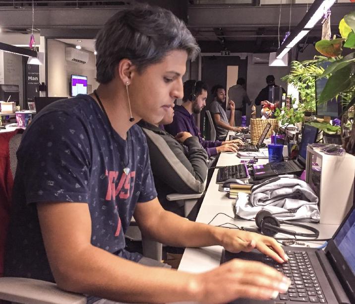 Foto mostra bancada de trabalho, toda decorada com plantas, e um membro da equipe de atendimento do Nubank digitando em um computador
