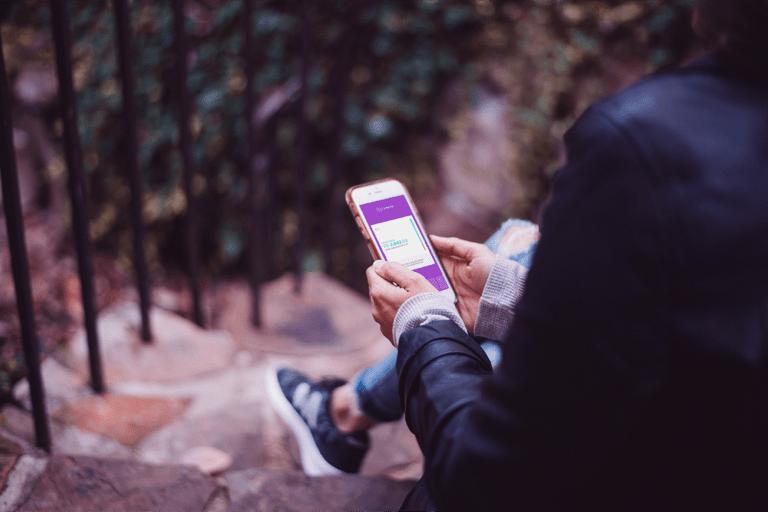 Pessoa sentada em uma escada ao ar livre segura um telefone com as duas mãos. Na tela, o app do Nubank aberto na aba de NuConta