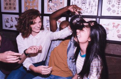Três amigos dando risada - duas moças e um rapaz - dando risada. Dois deles estão mexendo no cabelo de uma delas.
