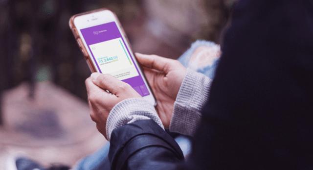NuConta: Pessoa sentada em uma escada ao ar livre segura um telefone com as duas mãos. Na tela, o app do Nubank aberto na aba de NuConta