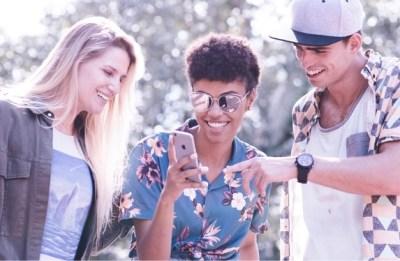 NuConta RDB Nubank: tr6es amigos sorrindo e olhando para um telefone