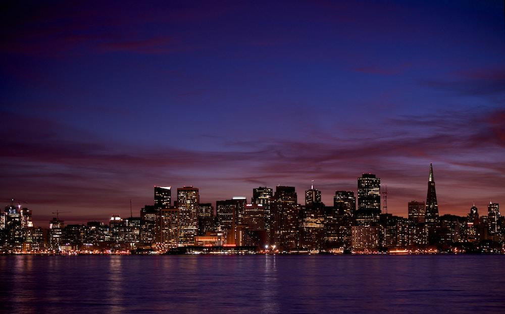 Foto de uma cidade à noite, com diversos arranha céus iluminados.