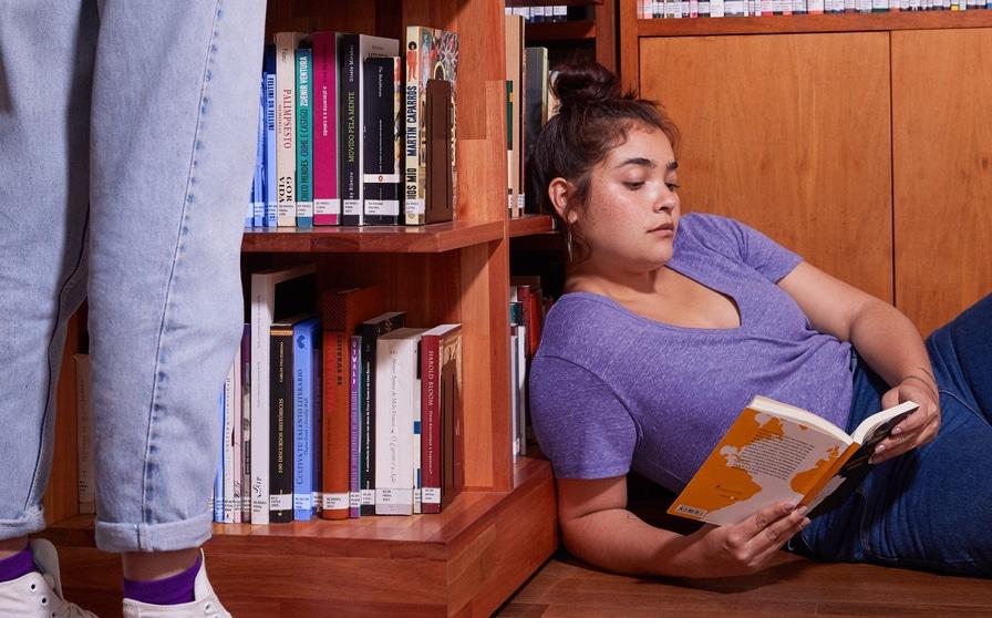 Como ler extrato FGTS: Jovem deitada no chão lendo um livro